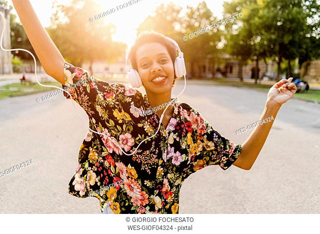 Happy fashionable young woman with headphones dancing outdoors at sunset