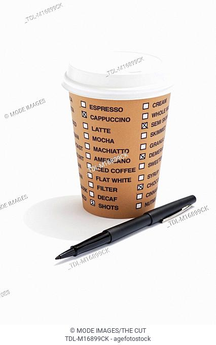 A takeaway drink cup with list of coffee options on it and a pen