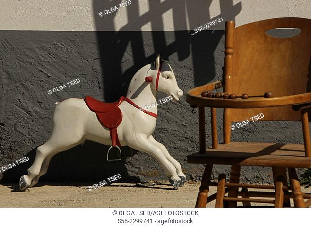 Antique shop, a wooden horse and a baby chair, Ponts, Lleida Province, Catalonia, Spain