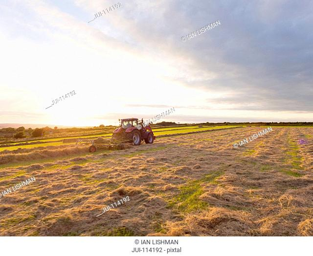 Rear View Of Tractor Baling Hay In Field At Sunset