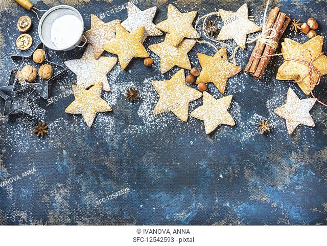 Gingerbread Christmas star shaped cookies with cinnamon, anise, nuts, baking molds and sugar powder on dark plywood painted background