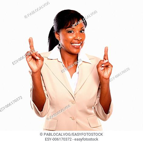 Pretty businesswoman smiling and crossing fingers against white background