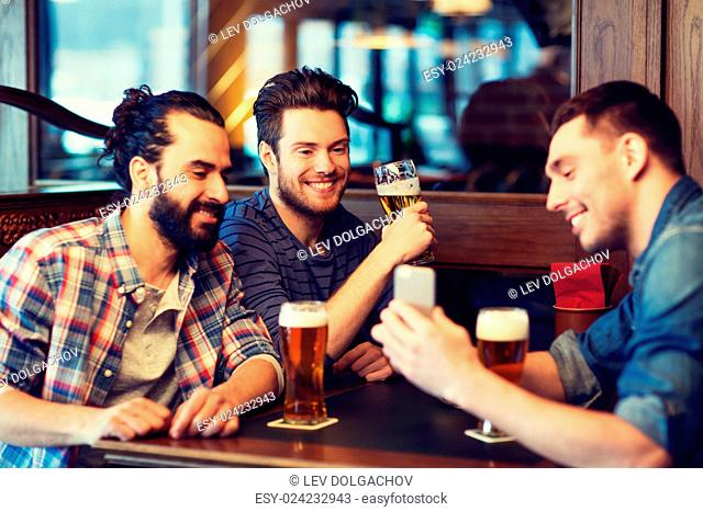 people, men, leisure, friendship and technology concept - happy male friends with smartphone drinking beer at bar or pub