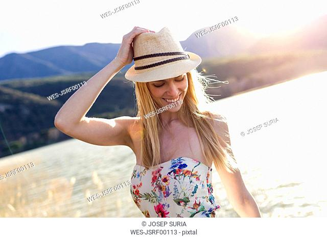 Smiling young woman wearing summer hat and top with floral design in front of lake