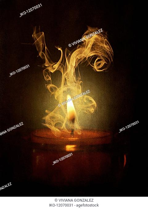 Smoke rising and swirling from lit candle