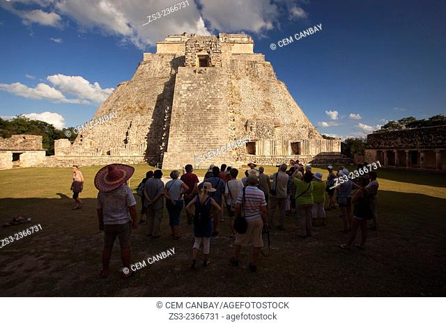 Tourists walking around the Pyramid of the Magician, Maya archeological site Uxmal, Yucatan, Mexico, Central America