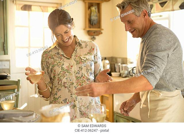 Playful mature couple baking in kitchen