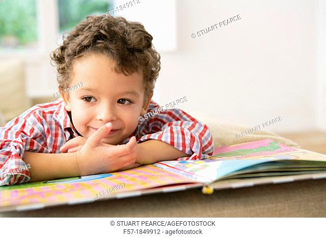 Four year old boy reading a book on the sofa