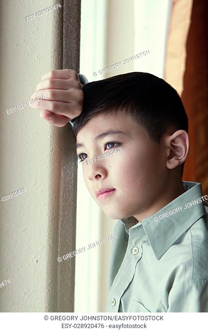 A young boy gazes out the window from inside