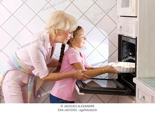 Grandmother and granddaughter putting food in oven