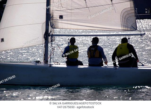 Three people sailing on a sailboat in Valencia, Spain, Europe