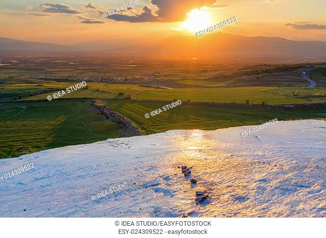 Sunset at the valley with glance surface on foreground Pamukkale Turkey