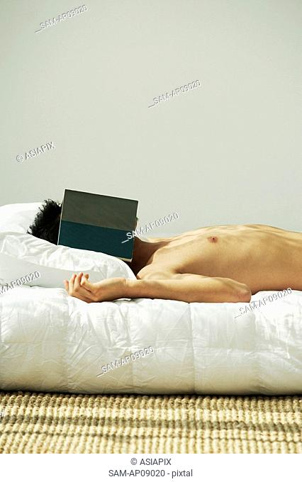 Young man lying in bed, face covered by a book
