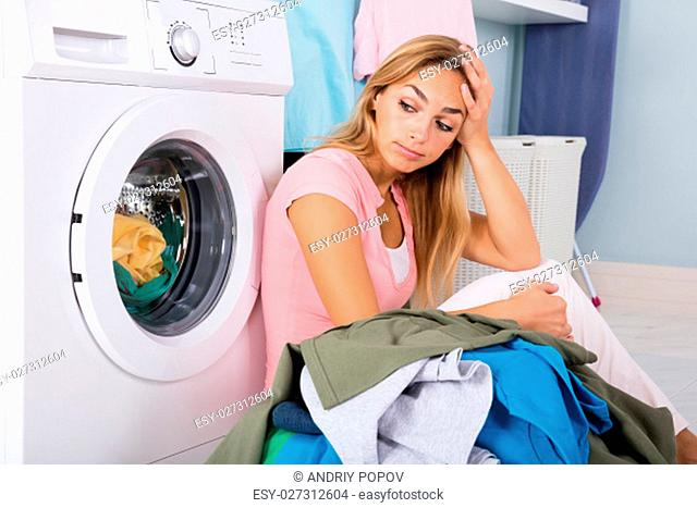 Unhappy Woman Showing Signs Of Fatigue Looking At Pile Of Dirty Clothes Near Washing Machine
