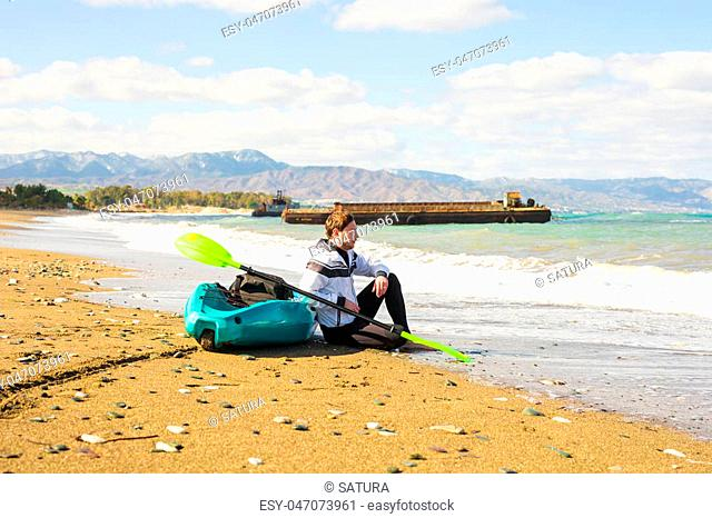 Man sitting on the beach with kayak. Traveling by sea. Leisure activities on the water