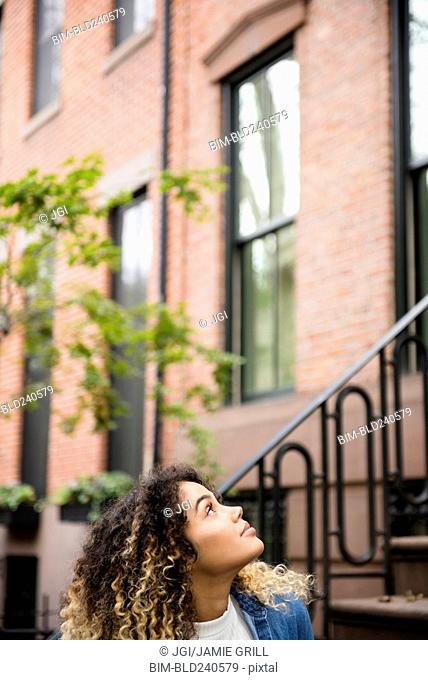 Curious Mixed Race woman looking up in city