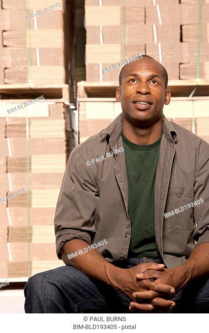 Black man sitting in warehouse