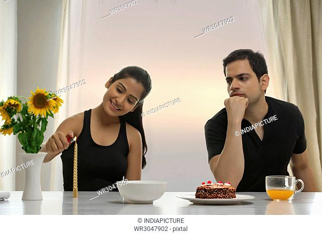 Serious man looking at woman lighting candle at table with cake