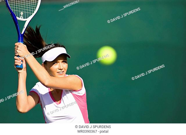 Tennis player focused intently on ball in match
