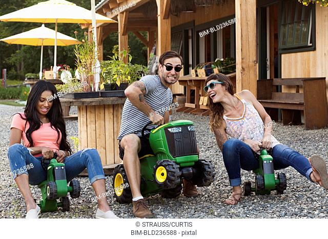 Friends playing on toy tractors