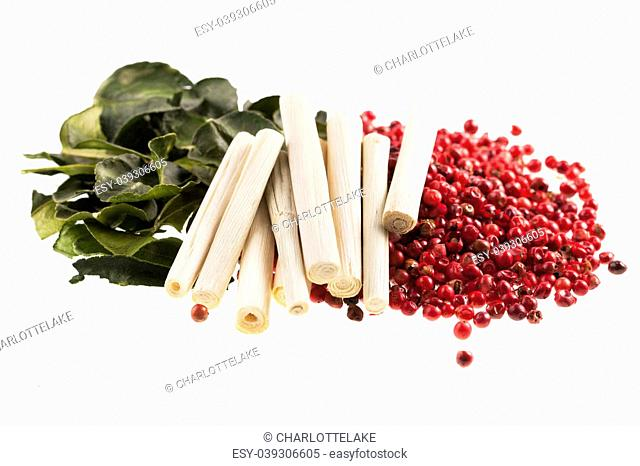 Thai cooking spices, kaffir lime leaves, lemon grass and pink peppercorns isolated on a white background