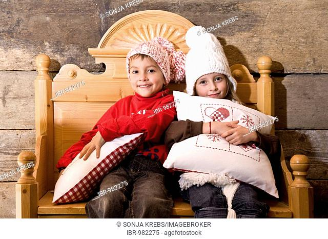 Two siblings are sitting on an old bench in a cottage