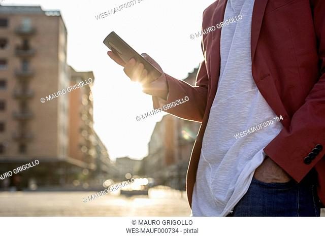 Young man with smartphone at backlight, partial view
