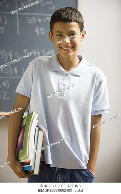Student with schoolbooks smiling for the camera
