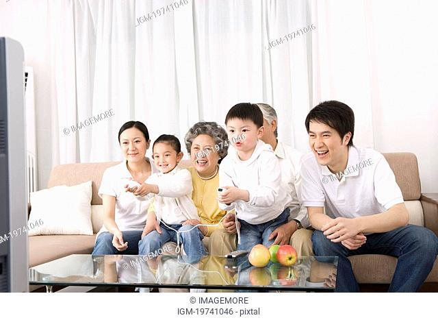 Grandparents and grandchild sitting on sofa playing video game, smiling
