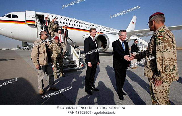 German Defence Minister Thomas de Maiziere (C) and Foreign Minister Guido Westerwelle (L) are welcomed by German Bundeswehr armed forces General Joerg Vollmer...