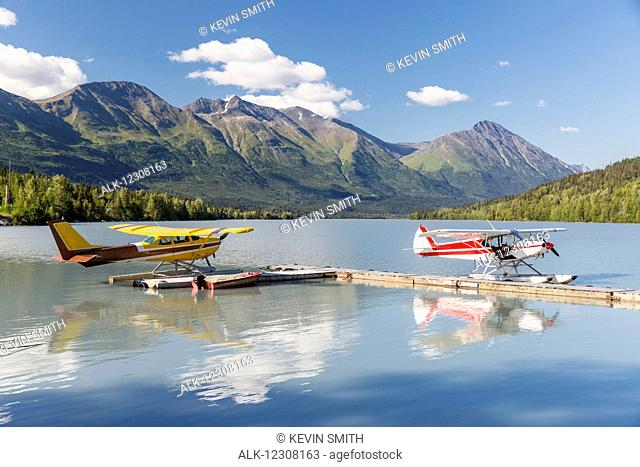 Two float planes docked at the Trail Lake Float Plane Base on a clear day, the Kenai Mountains in the background, Kenai Peninsula, Southcentral Alaska, USA