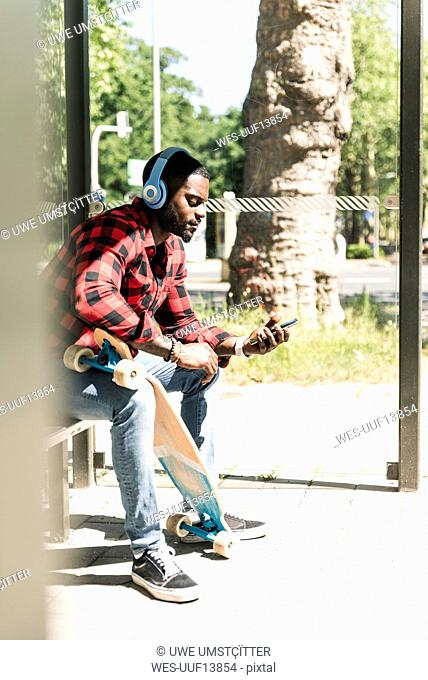 Cool young man with headphones, waiting at bus stop
