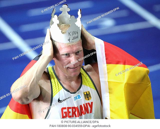 08.08.2018, Berlin: Athletics, European Championships in the Olympic Stadium: Decathlon, 1500 m, Men, Arthur Abele from Germany celebrates gold and puts on a...