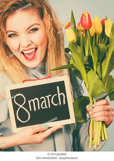 International women day. Beautiful woman blonde hair fashion make up holding red yellow tulips and frame board with message 8 march. Toned image