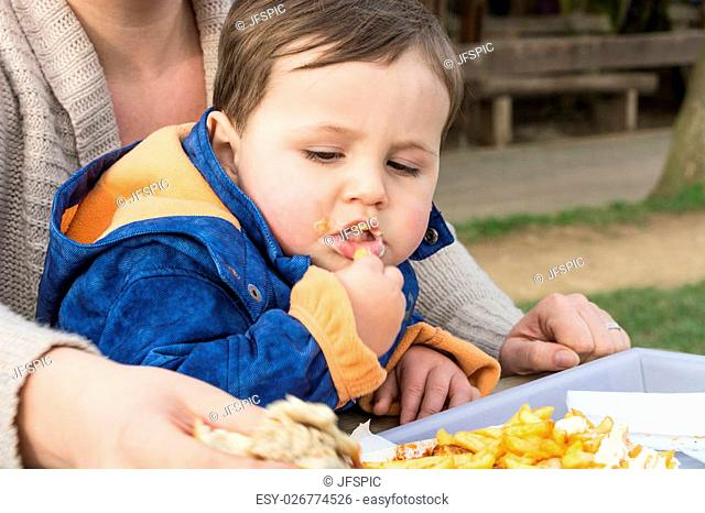 Child eats sausage with french fries from a paper plate