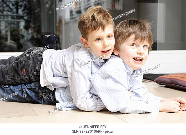 Boys hugging on living room floor
