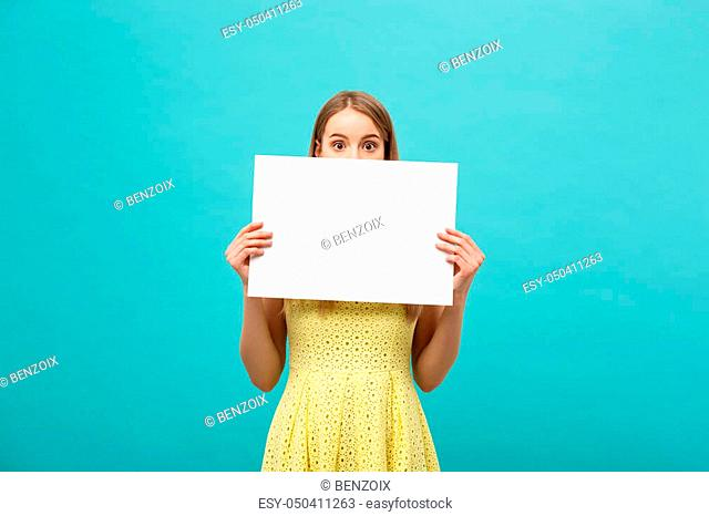 Closeup portrait, young woman in yellow dress holding white plain paper with shocked expression at what she sees, isolated blue background