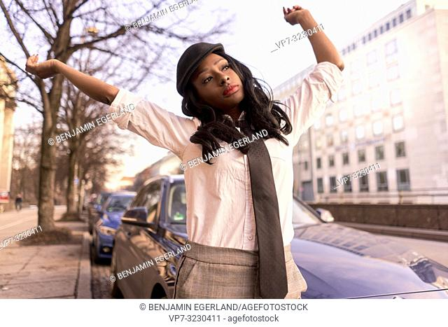 stylish woman dancing with arms in evening sunlight at street, wearing retro clothes, business look, African Angolan descent, in city Munich, Germany