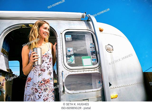 Young woman with coffee looking out from airstream doorway