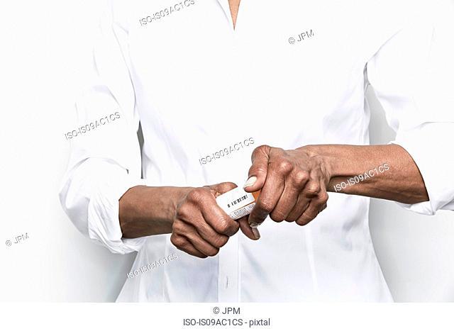 Senior woman opening medicine
