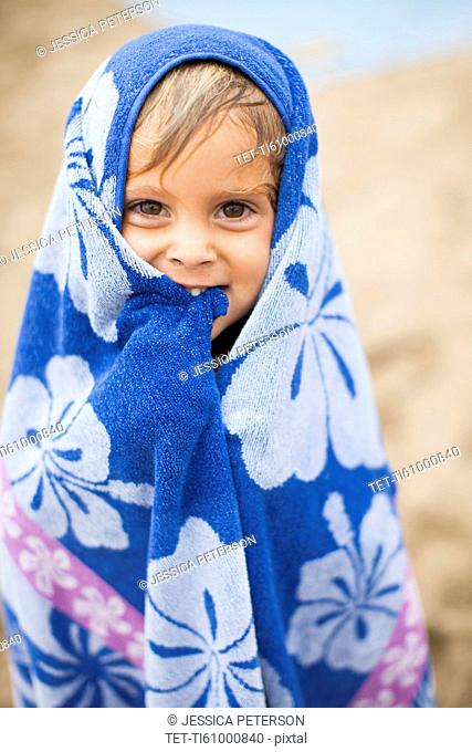 Baby girl (2-3) wrapped in towel on beach
