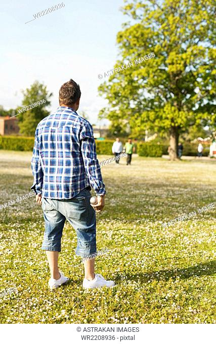 Full length rear view of man looking at friends while playing boule at park