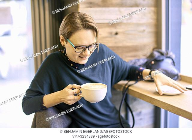 woman drinking coffee indoors in café in Munich, Germany