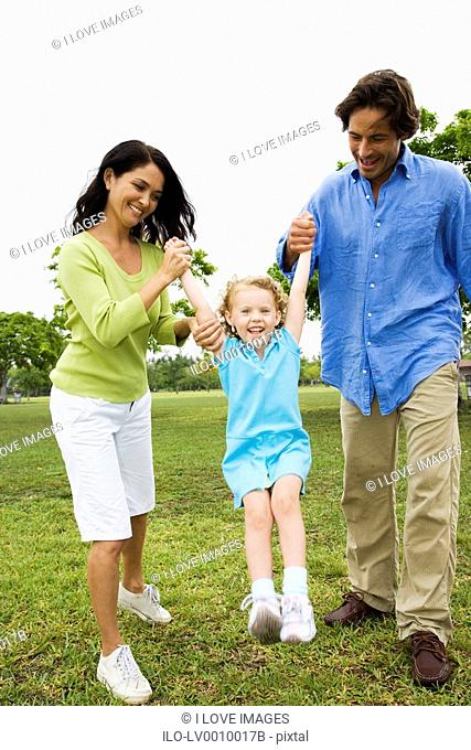 parents playing with their daughter in the park