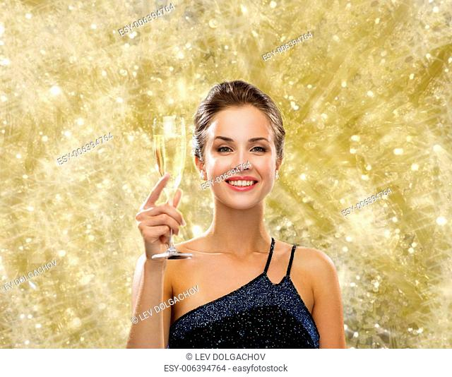 party, drinks, holidays, people and celebration concept - smiling woman in evening dress with glass of sparkling wine over yellow lights background