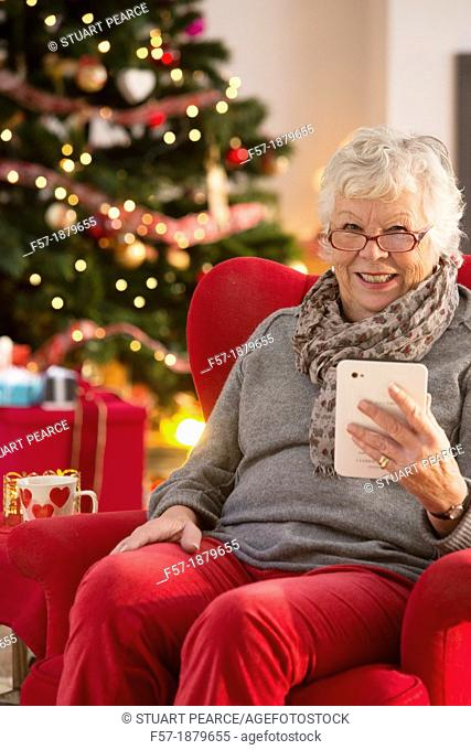 Senior woman communicating with family on her tablet computer at Christmas time