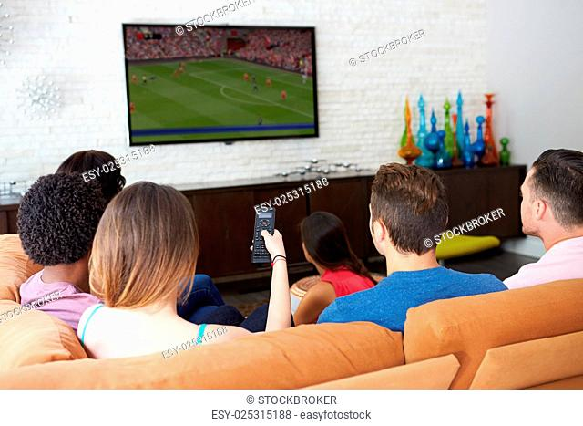 Group Of Friends Sitting On Sofa Watching Soccer Together