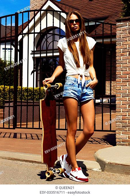 Girl in white vest and jeans shorts poses with longboard