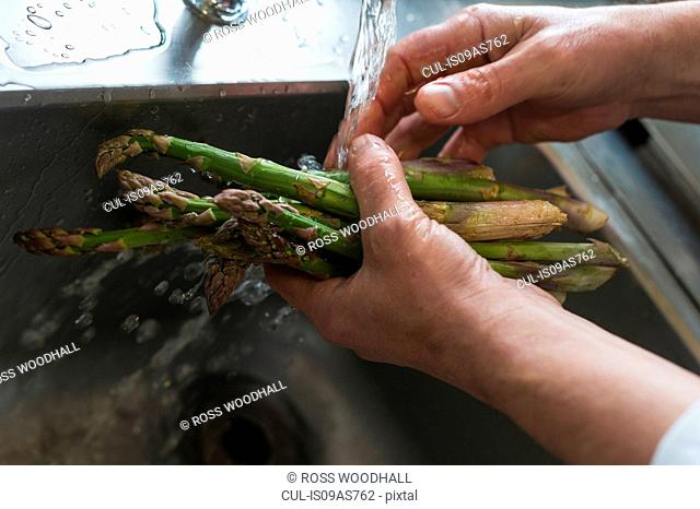 Washing asparagus, focus on hands