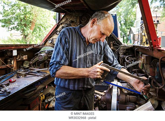Blacksmith in his workshop on a working barge, at a work bench using a hacksaw